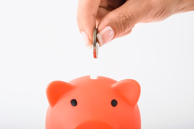 Hand dropping coin in red piggy bank Free Photo