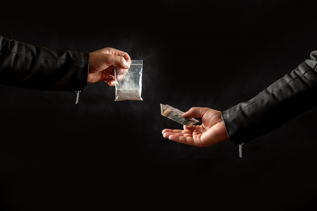 Hand of a drug addict with money buying a dose of cocaine Premium Photo