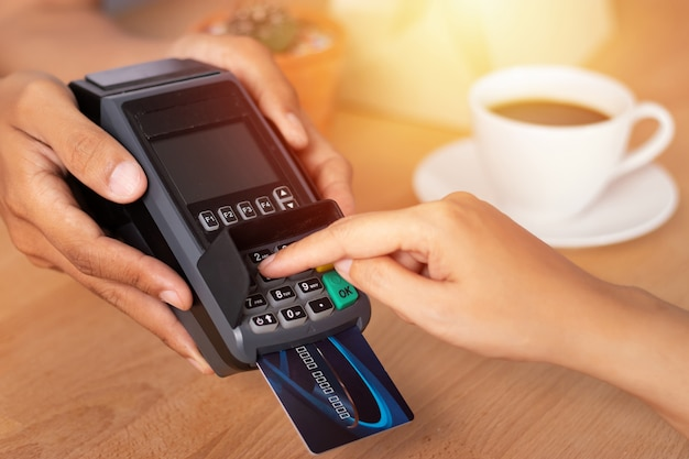 Hand entering credit card pin code for security password in credit card swipe machine Premium Photo