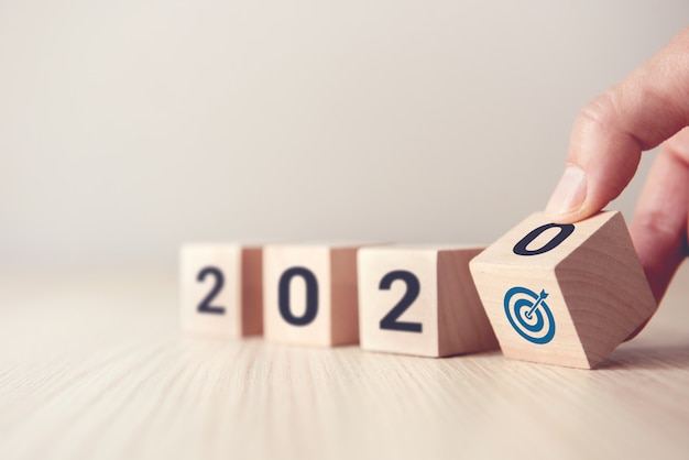 Premium Photo | Hand flip over wood wooden cubes with new year 2020 and goal icon concept.