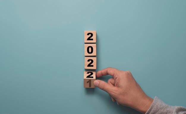 파란색 배경, 메리 크리스마스, 해피 뉴가 어 준비 개념에 2021을 2022로 변경하려면 나무 블록 큐브를 뒤집는 손. 프리미엄 사진