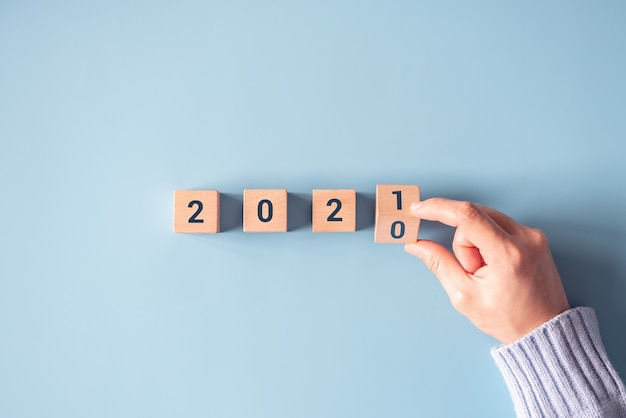 Hand flipping wooden blocks for change year 2020 to 2021 on blue paper background. Premium Photo
