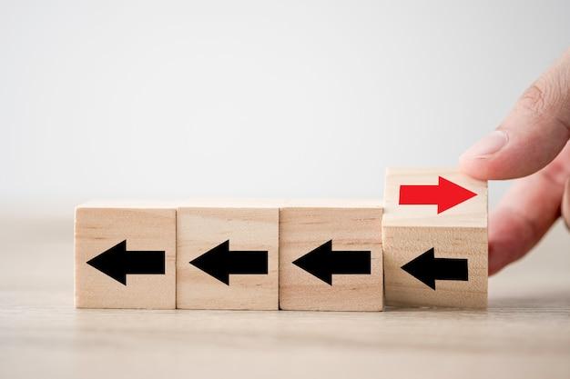 Рука переворачивает деревянную стрелку кубического блока от смены слева направо для срыва бизнеса и другой мыслительной идеи. Premium Фотографии