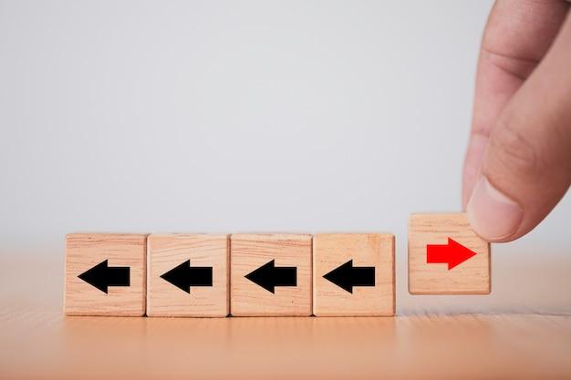 Рука переворачивает деревянную стрелку блока куба красная от изменения слева направо для срыва бизнеса и другой идеи мышления. Premium Фотографии