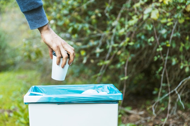 Handgetting rid of paper cup in rubbish Free Photo