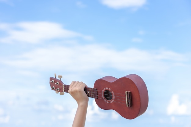 The hand of the girl holding the guitar in the background is a bright sky, giving a feeling Premium Photo