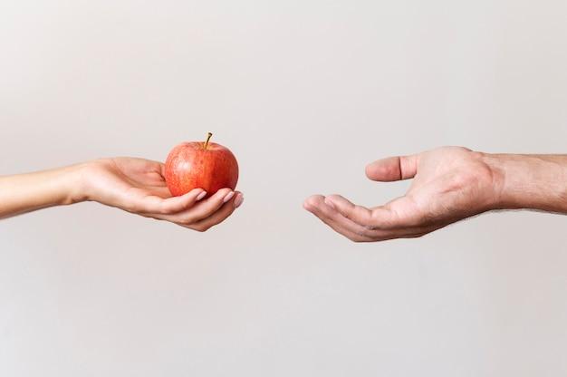 困っている人にリンゴを与える手 Premium写真
