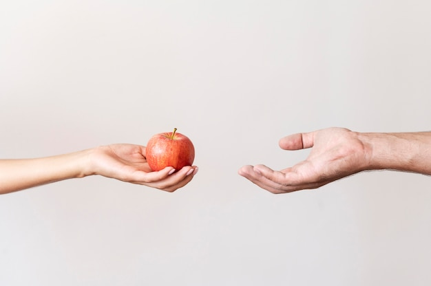 Hand giving apple fruit to needy person Premium Photo