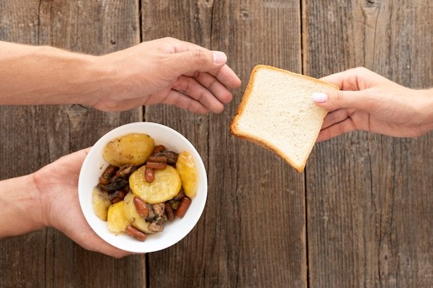 Hand giving bowl of food and bread to needy person Free Photo