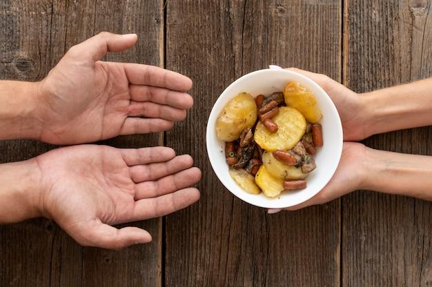 Mano che dà la ciotola del cibo donata alla persona bisognosa Foto Gratuite