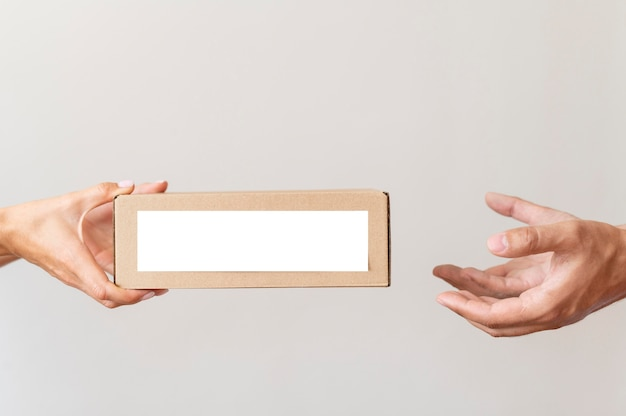 Hand giving donation box to needy person Free Photo