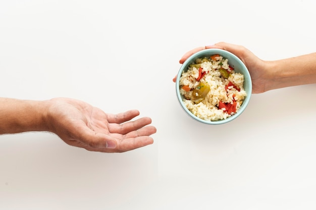 Hand giving food bowl to needy person Free Photo