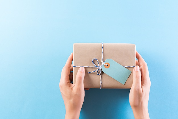 Hand giving a gift box with greeting card Premium Photo