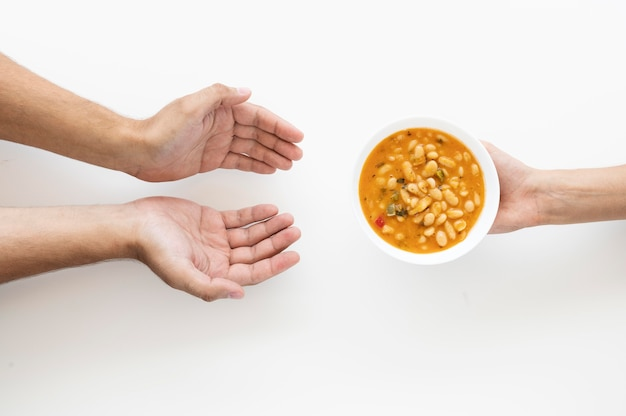 Hand giving soup bowl to needy person Free Photo