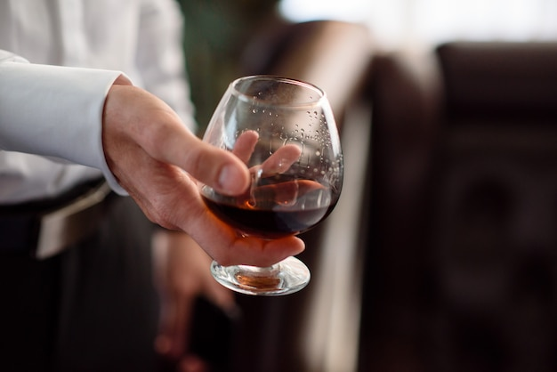 Hand, a glass of cognac Premium Photo