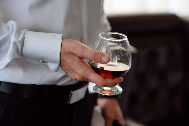 Hand, a glass of cognac Premium Photo