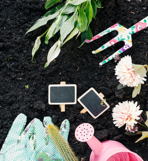 Hand gloves; watering can; flowers; gardening fork; and plants on black dirt Free Photo