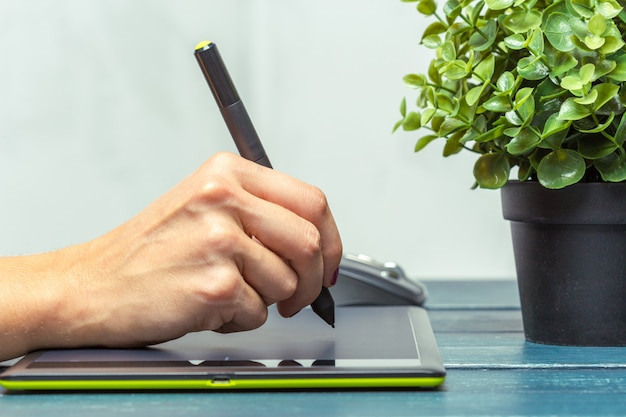 Hand of graphic designer working with stilus and tablet Premium Photo