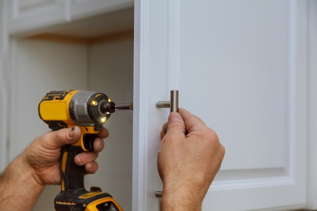 Hand on handle installation door in kitchen cabinet with a screwdriver Premium Photo