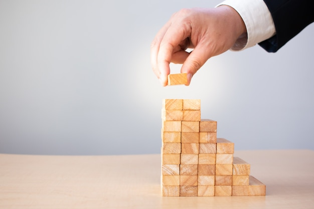 Hand held wooden blocks businessmen stacked together to develop a stair step, risk management, to the growth in planned success. Premium Photo