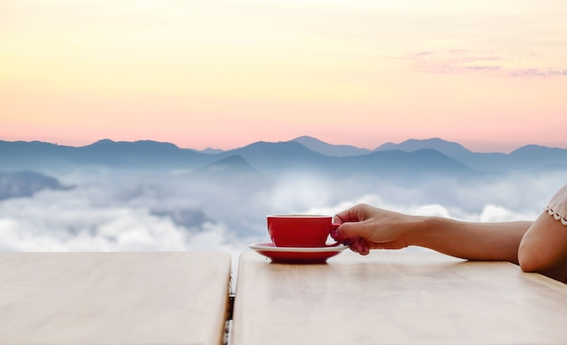 Hand hold coffee cup and coffee of morning sun Premium Photo