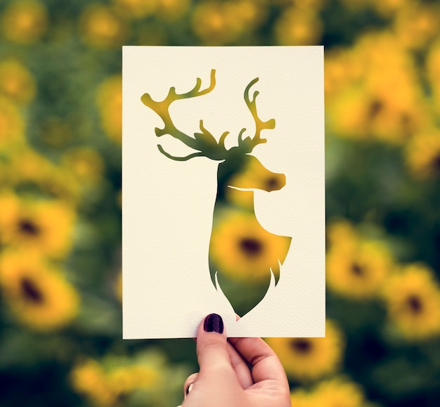 Hand hold deer with antlers paper carving with sunflower backgro Free Photo