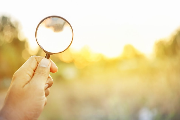 Hand hold magnifying glass on orange light ray Premium Photo