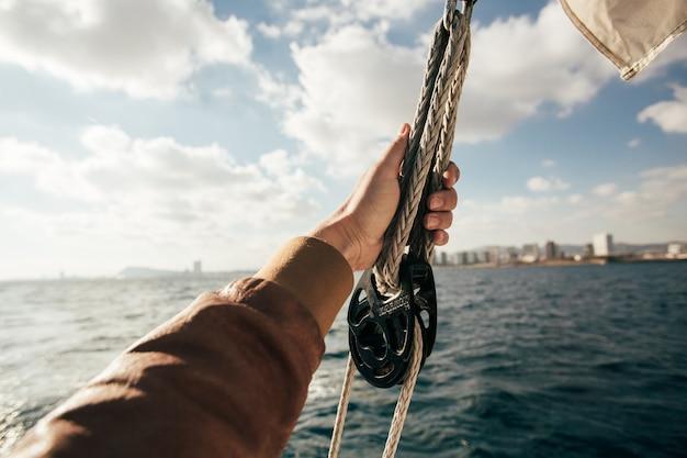 Tenere in mano la vela o la corda sullo yacht Foto Gratuite