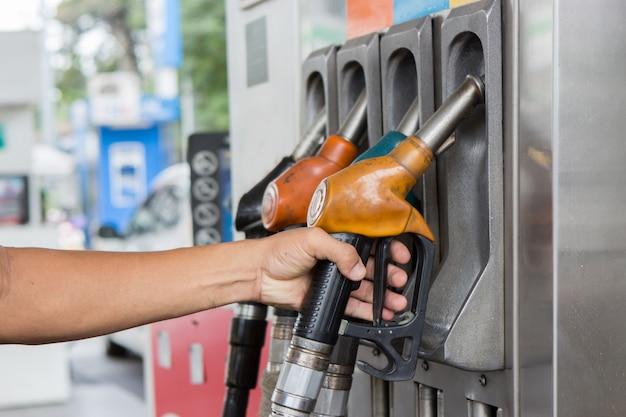 Hand hold petroleum gasoline on station Premium Photo