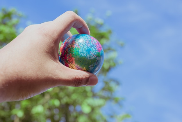 Hand hold plastic of planet earth on nature background. save the world concept. Premium Photo