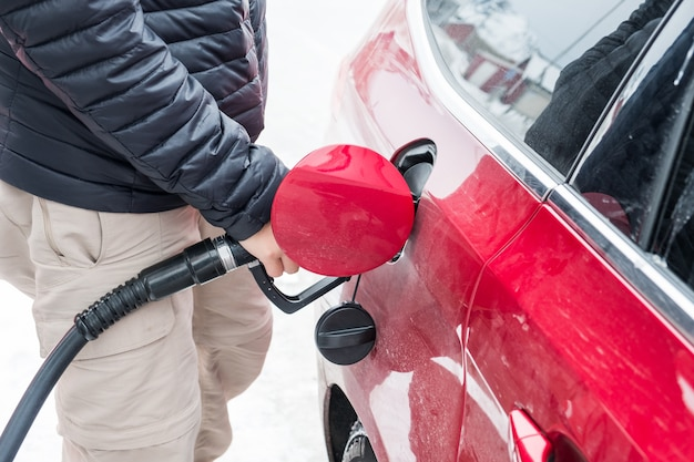 Hand hold refueling nozzle self-service in fuel tank at fuel station Premium Photo