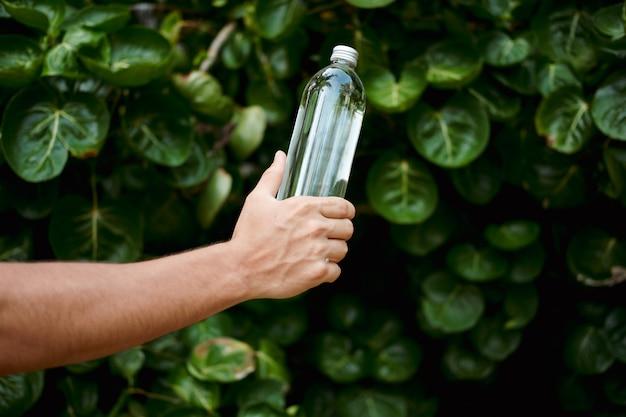 Hand hold water transparent glass reusable bottle Premium Photo