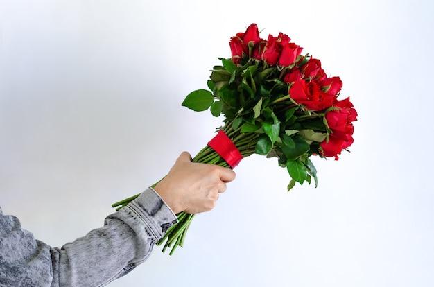 Рука, держащая букет красных роз, изолированные на белом фоне для годовщины или концепции дня святого валентина. Premium Фотографии