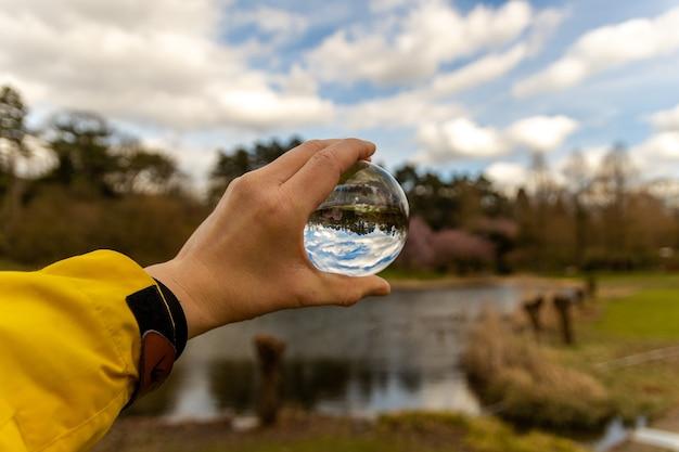 自然の中でガラス球を持っている手 無料写真