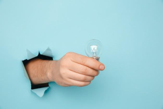 Рука лампочку от разорванного отверстия в синей бумаге. концепция экономии энергии Premium Фотографии