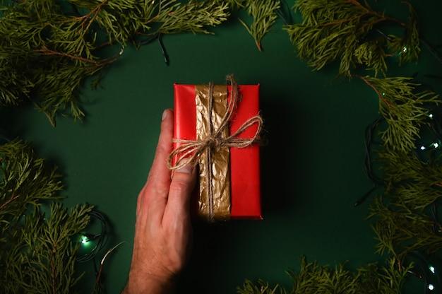 Рука, держащая новогодний подарок на темно-зеленом фоне рождества. Premium Фотографии