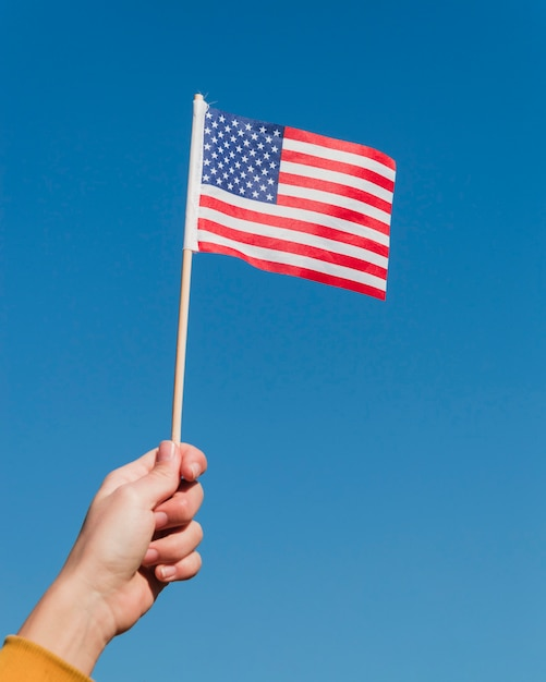 Hand holding american flag on blue sky Free Photo