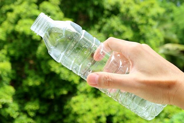 Рука пустую пластиковую бутылку питьевой воды с зеленой листвой на заднем плане Premium Фотографии