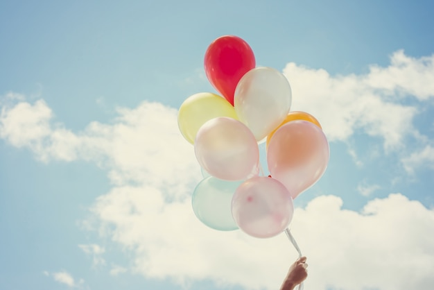 Hand holding balloons of different colors Free Photo