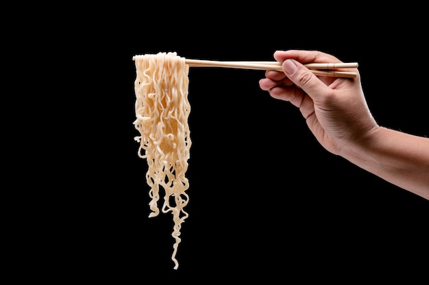 Hand holding bamboo chopsticks and fork over instant noodles Premium Photo