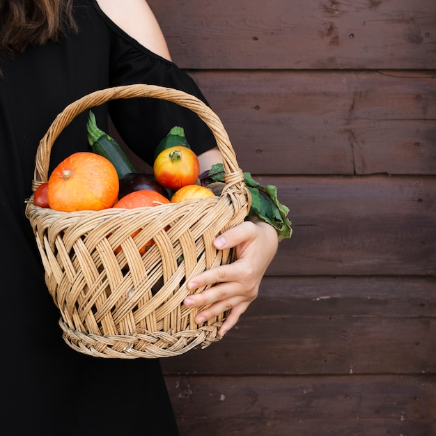 Hand holding basket with vegetables Free Photo
