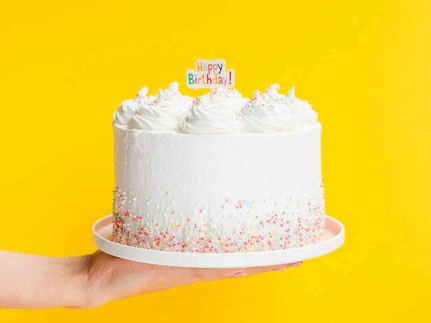 Hand holding big white birthday cake Premium Photo