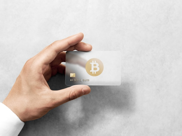 Hand holding bitcoin card template with embossed gold logo Premium Photo