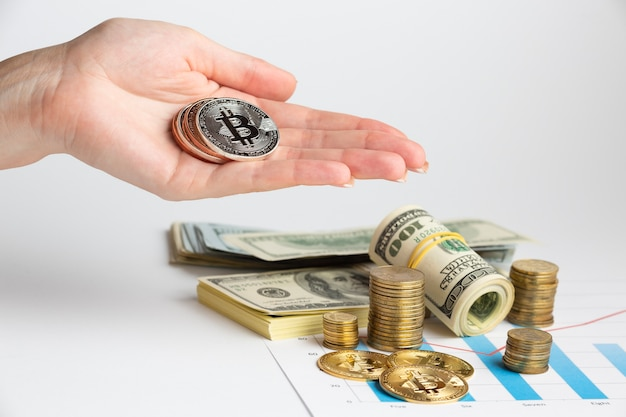 Hand holding bitcoin above money stack Free Photo