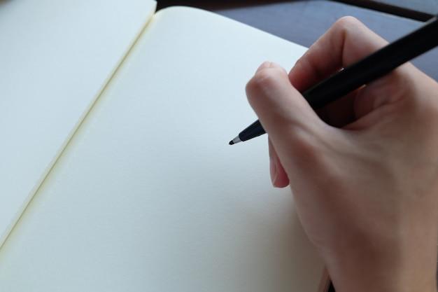Hand holding black pen Free Photo