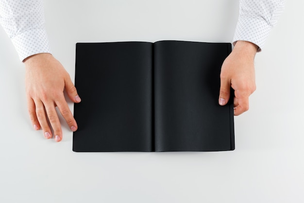 Hand holding blank opened book mock up Premium Photo