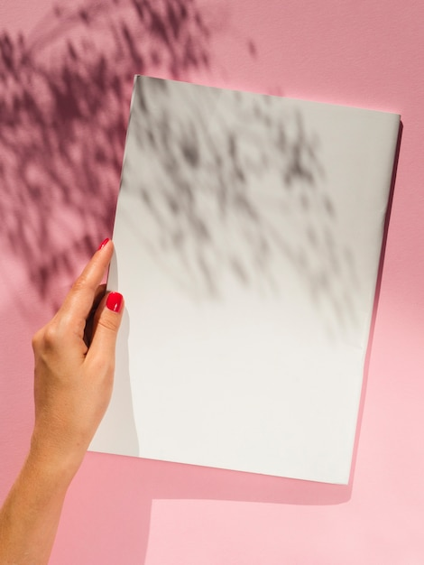 Hand holding blank paper with shadows Free Photo