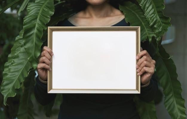 Hand holding blank photo frame Premium Photo