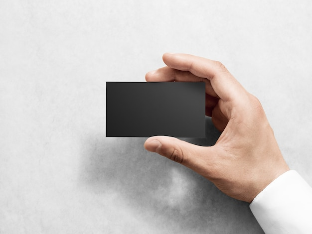 Рука держит пустой простой черный макет дизайна визитной карточки Premium Фотографии