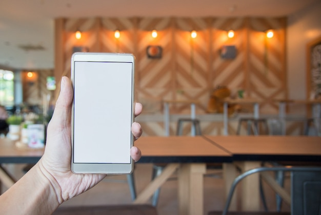 Hand holding blank screen of smart phone with blurred sitting on cafe background Premium Photo